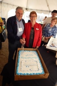 Gibbons Deputy Mayor Louise Bauder helps Fort Air Partnership Chair Keith Purves cut the cake marking the grand opening June 16 of the new Gibbons Air Monitoring Station.