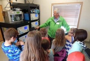 The grand opening of the new Gibbons Air Monitoring Station included school tours on June 15. Here, Network Manager Harry Benders shows the station's analyzers to Grade 4 students from Landing Trail school.